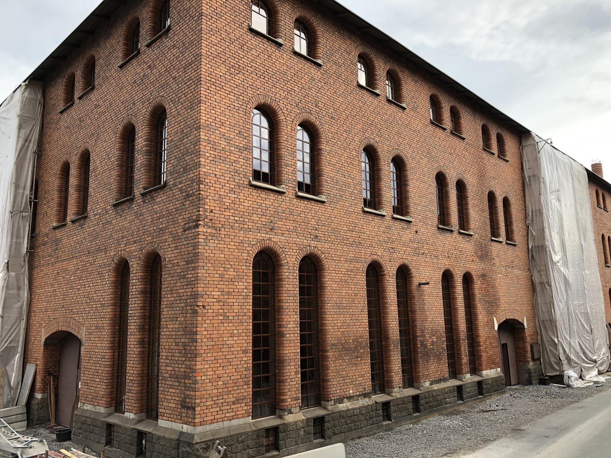 Industrifastighet med stora spröjsade kyrklika järnfönster efter renovering.